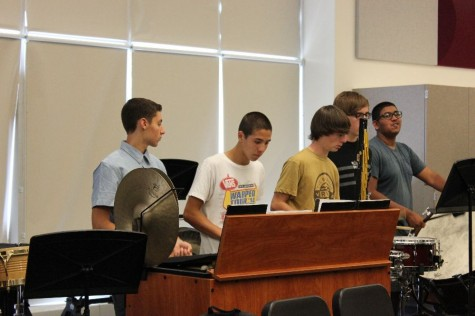 Percussionists in Concert Band work together while playing through a piece.