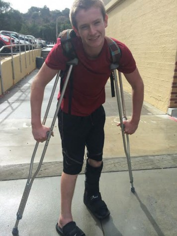 Cunningham walking around Carlmont campus on crutches.