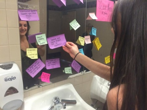 Erica Aldanese looking at the sticky notes in the U-hall bathroom