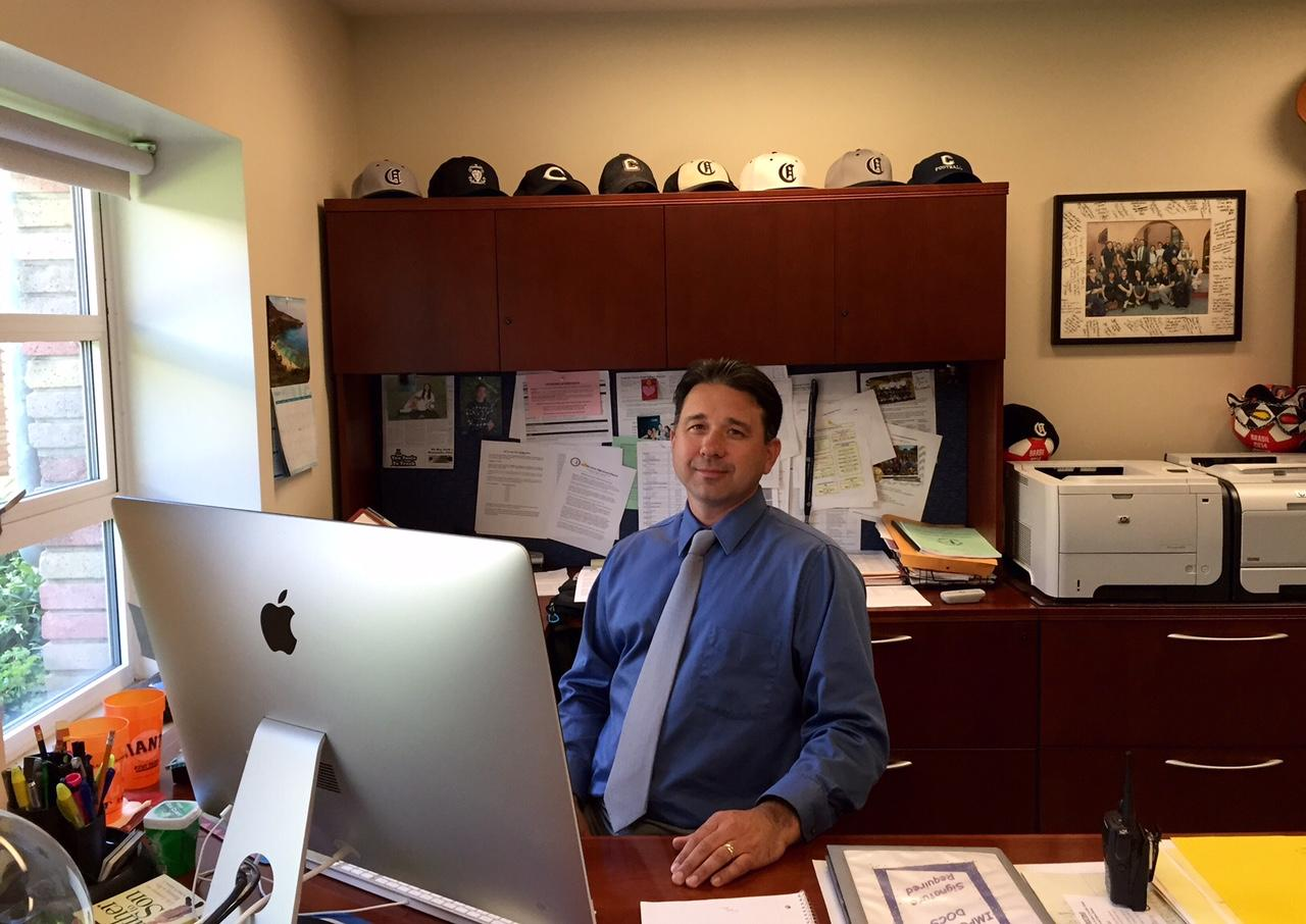 Crame sits in his office, where he works to make sure that the school runs smoothly.