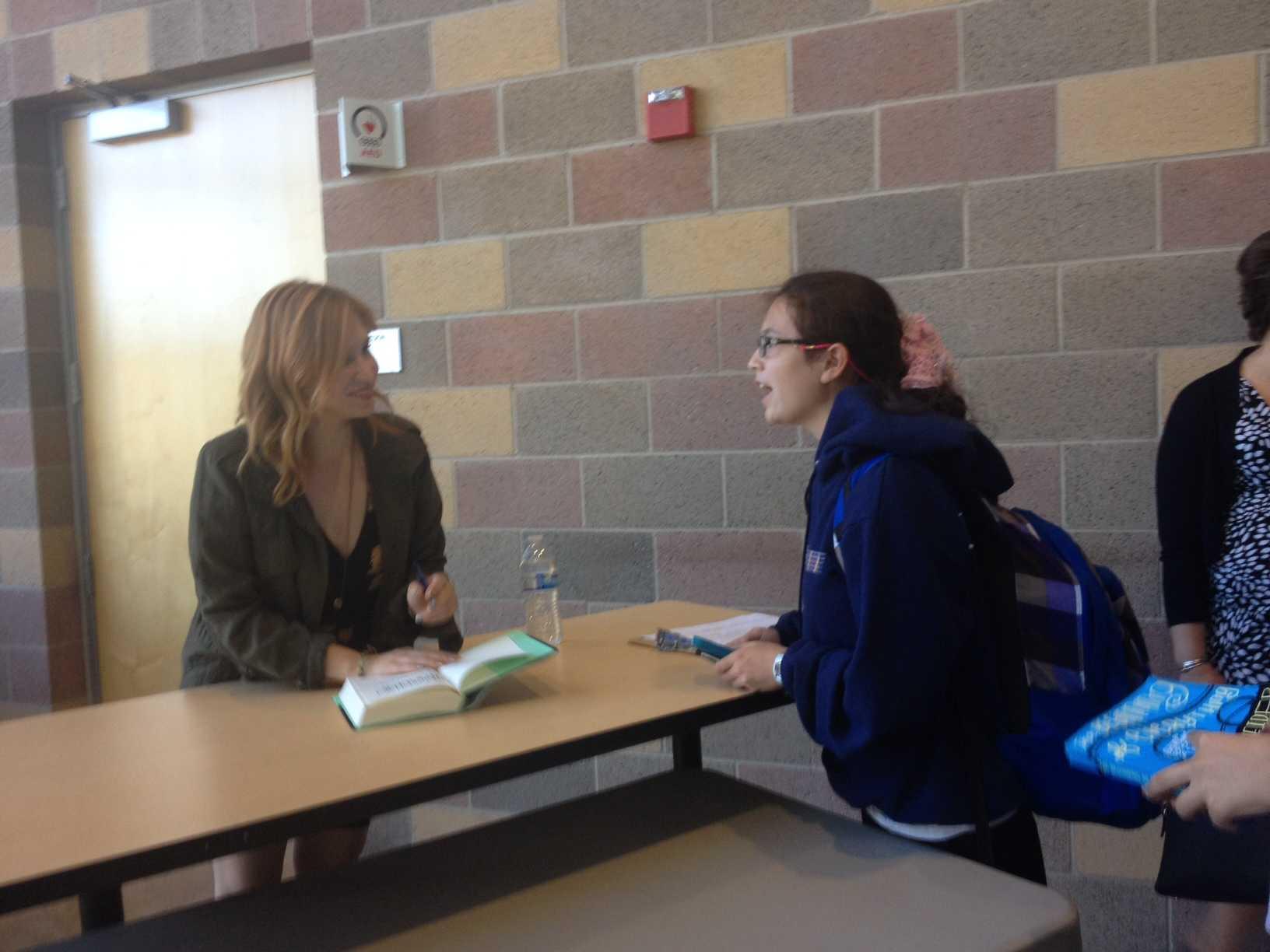 Freshman Alyssa Higdon meets Schneider after the book talk to get Schneider's autograph.