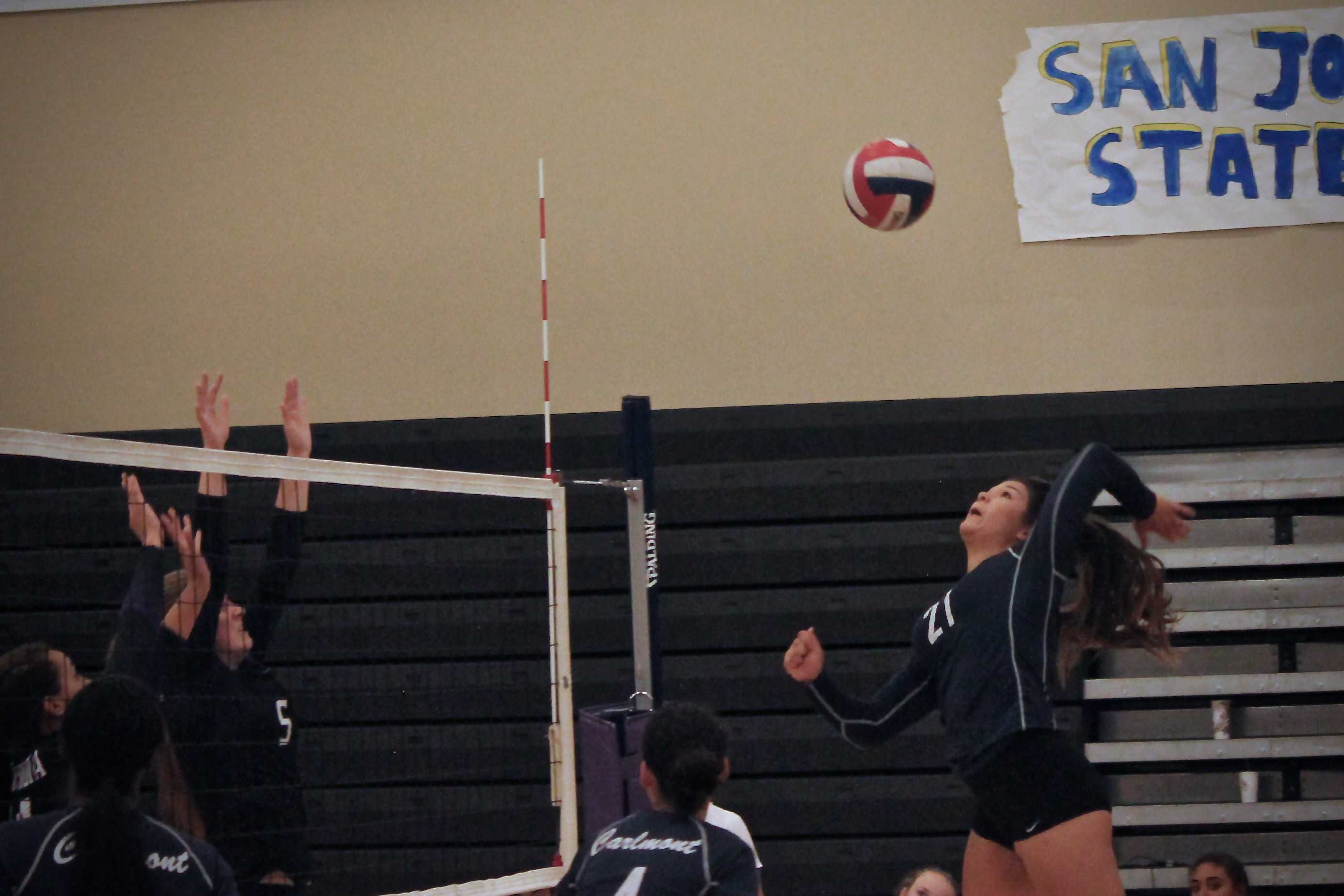 Senior Elena Mateus (21) swings hard for a deep-corner kill against the Sequoia Cherokees.