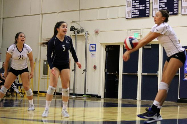 Seniors Elena Mateus (21) and Erin Alonso (5) encourage teammate Maya McClellan (10) to pass the ball.