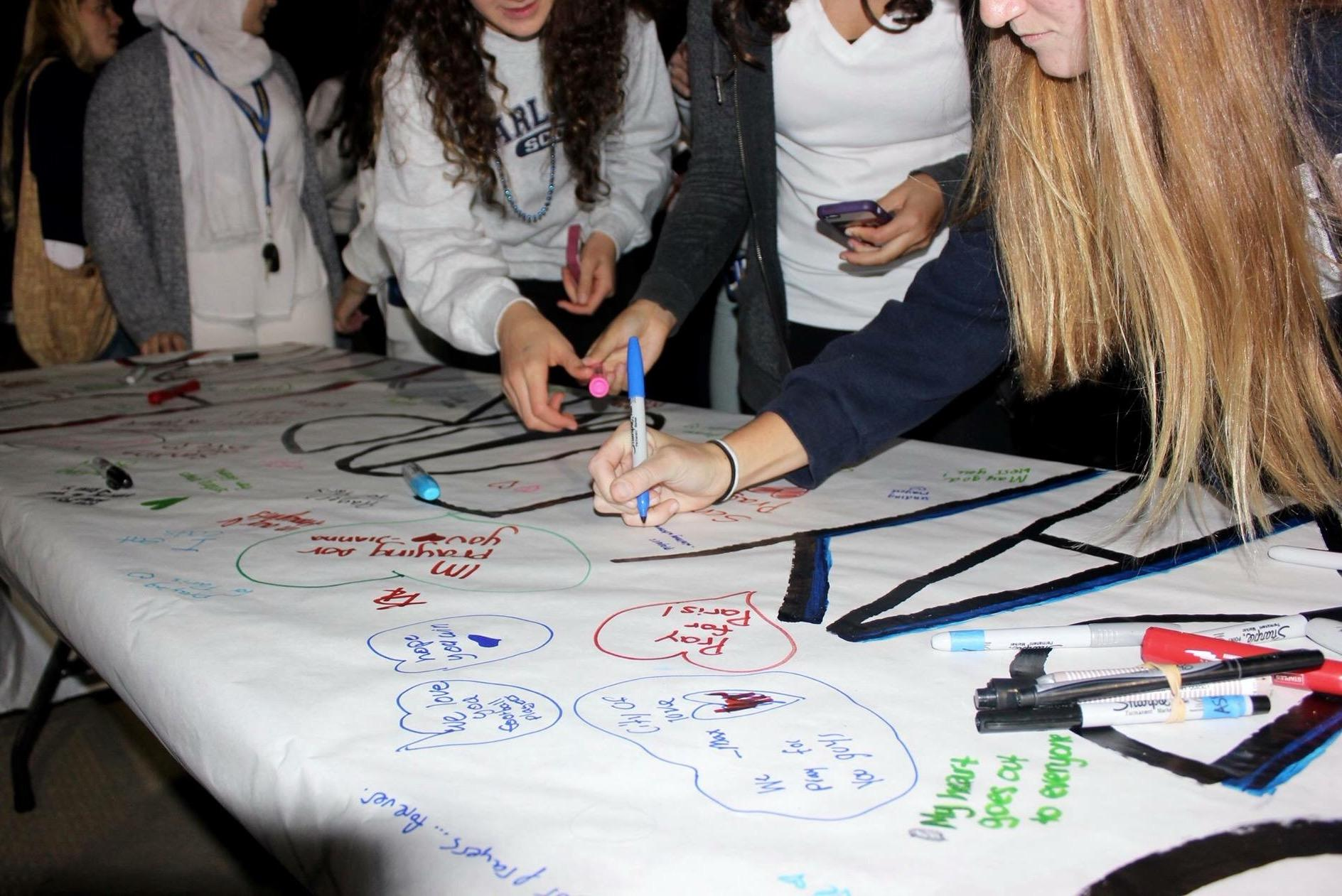 Students sign a banner in remembrance of the lives that were lost in the attacks in Paris.