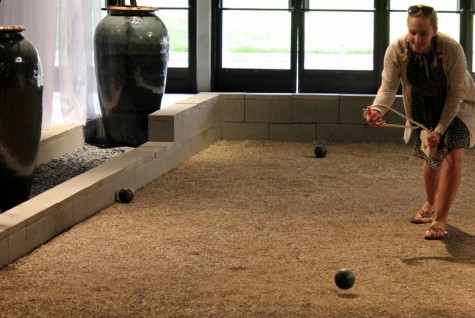 A visitor plays on the bocce ball court within an indoor garden display.