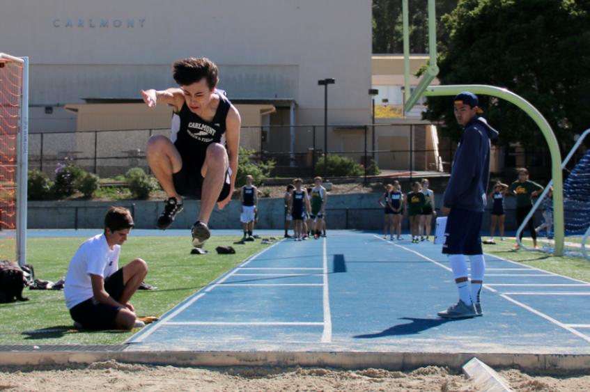 Junior+Eli+Brenman+leaps+through+the+air+and+lands+a+clean+long+jump.