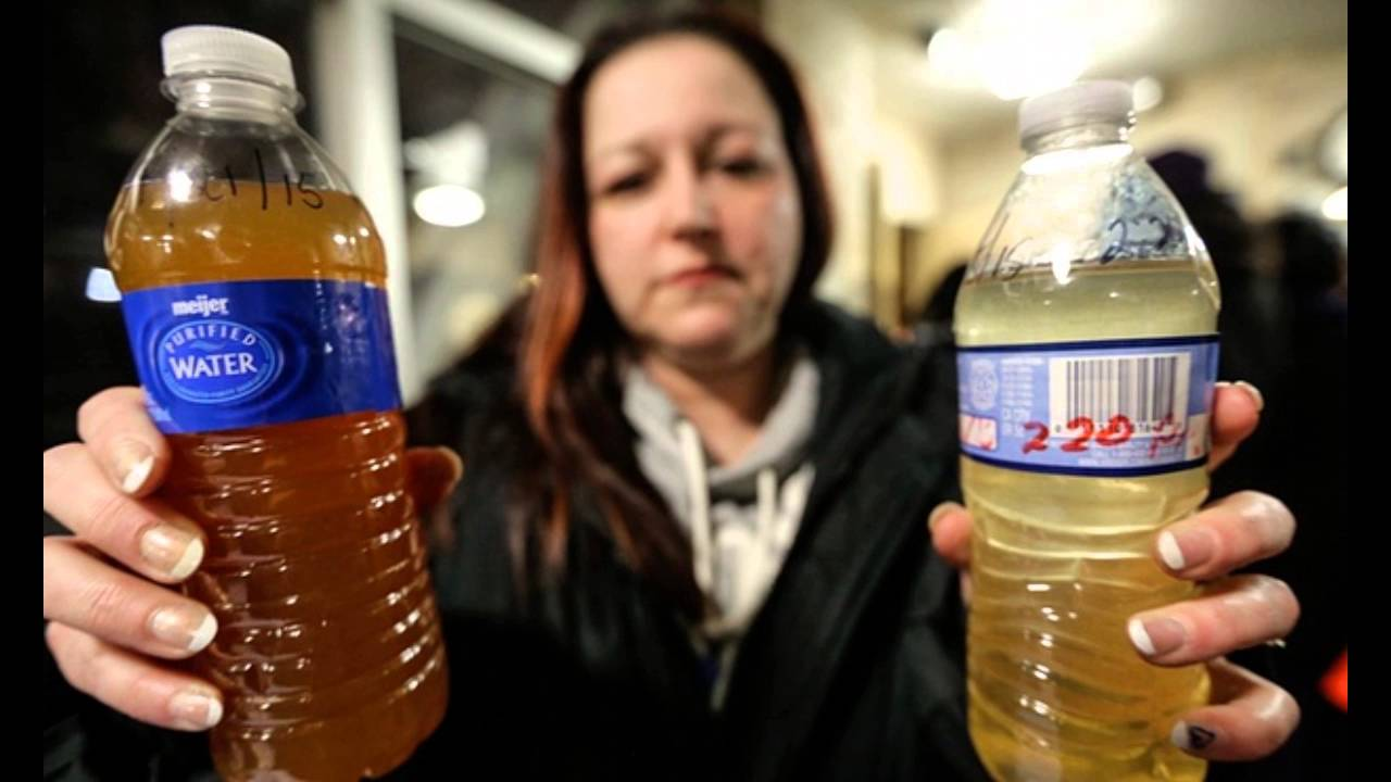 A woman holds up bottles filled with the poisoned water that has been circulating through Flint, Michigan's water pipes.