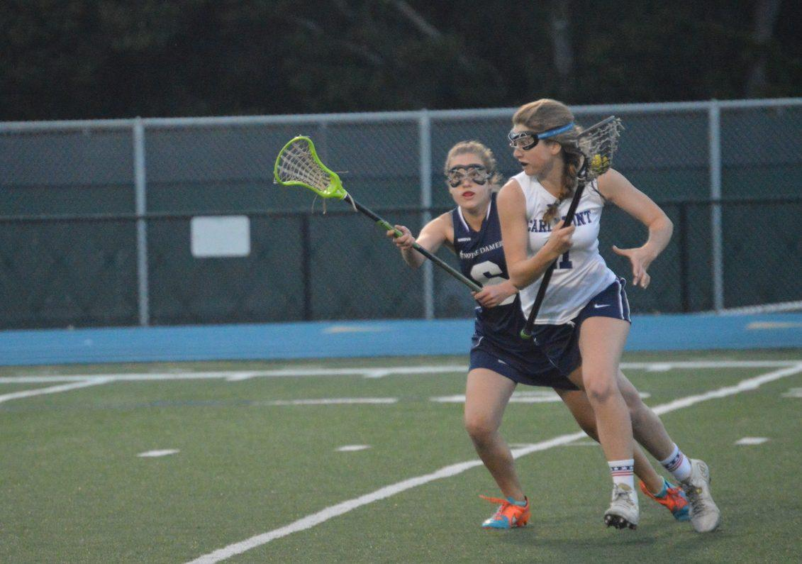 Junior Caroline Concilla cradles the ball and runs up the field.