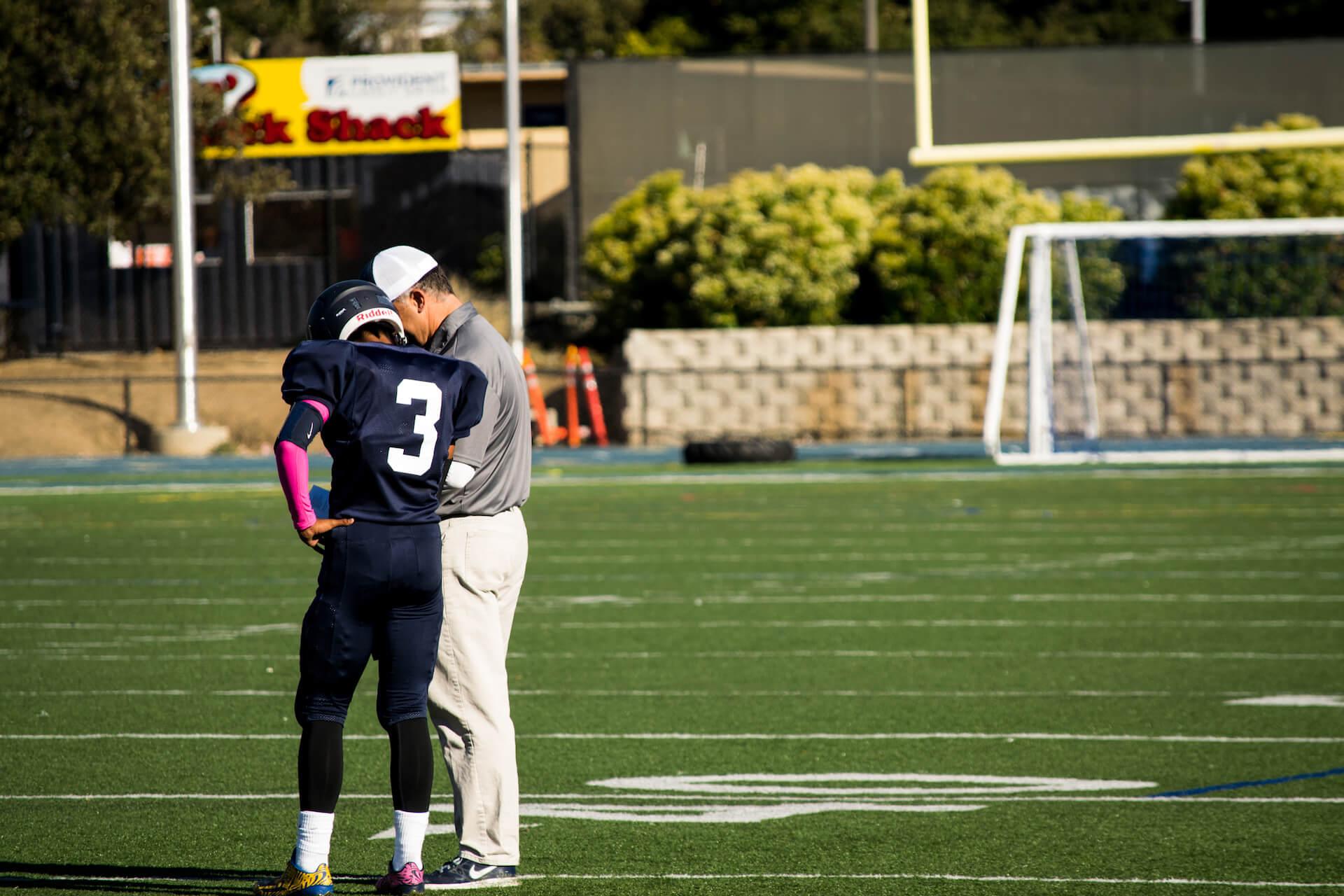 Quarterback, Simon Tara, discusses the game plan with coach, Bruce Douglas during a timeout.
