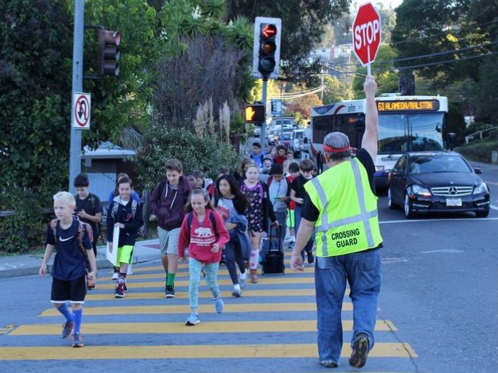Local crossing guard, Edward Henken, helps San Carlos students safely cross the street to school.