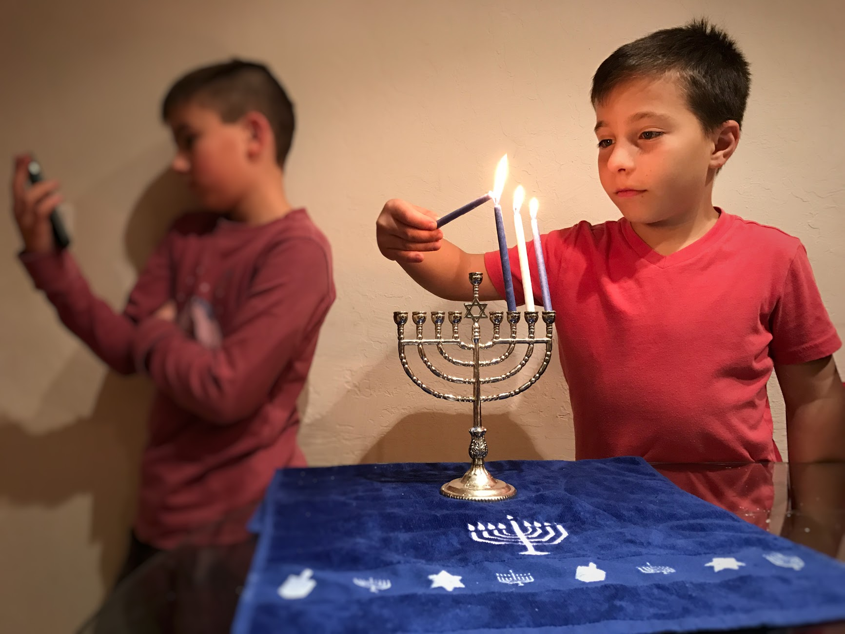 A 9-year-old boy is lighting a Menorah while the other is in the back on a device because he doesn't find it important.