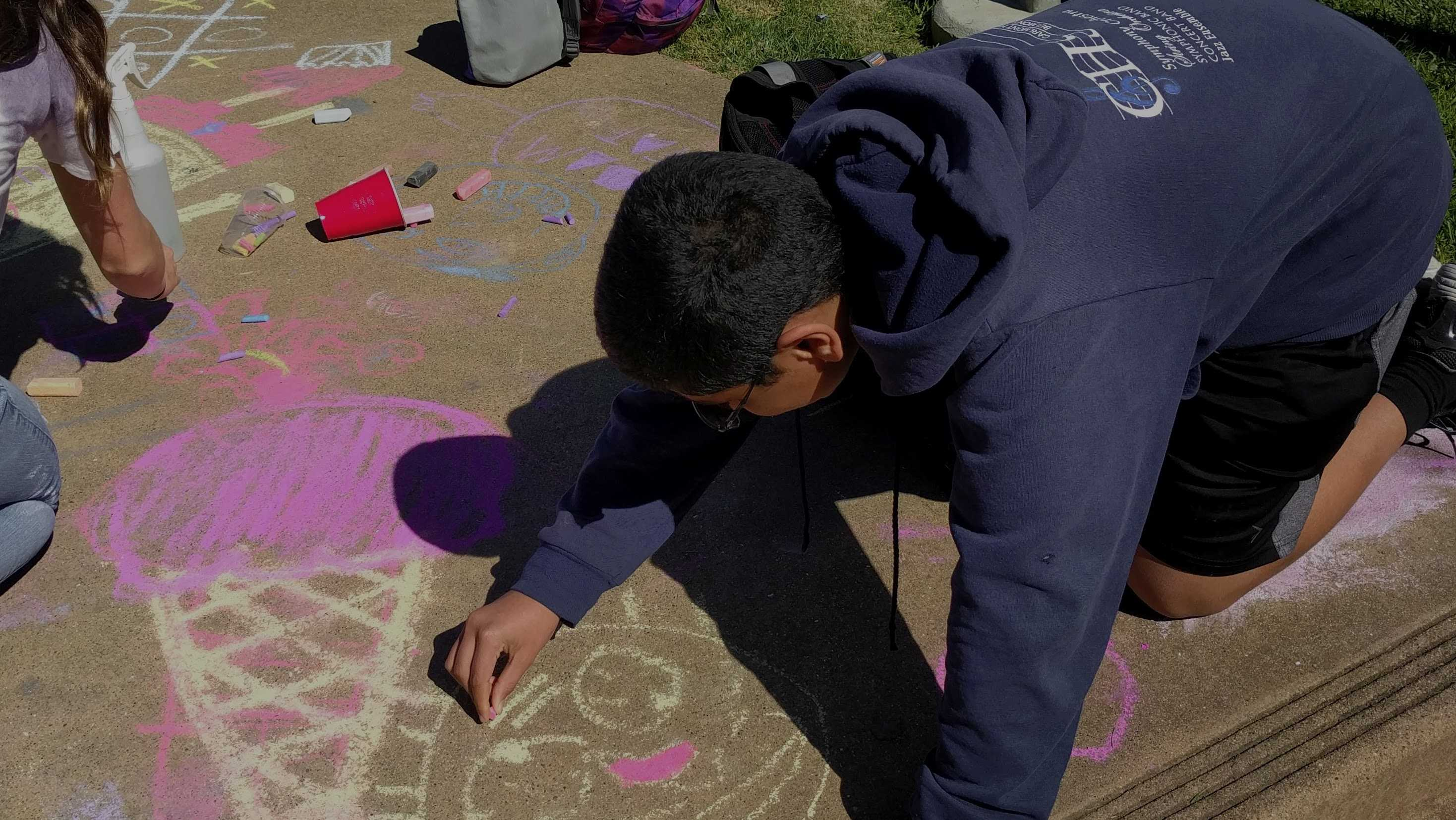 Sophomore Joshua Mathew draws a happy face during the Chalk for Happiness event..
