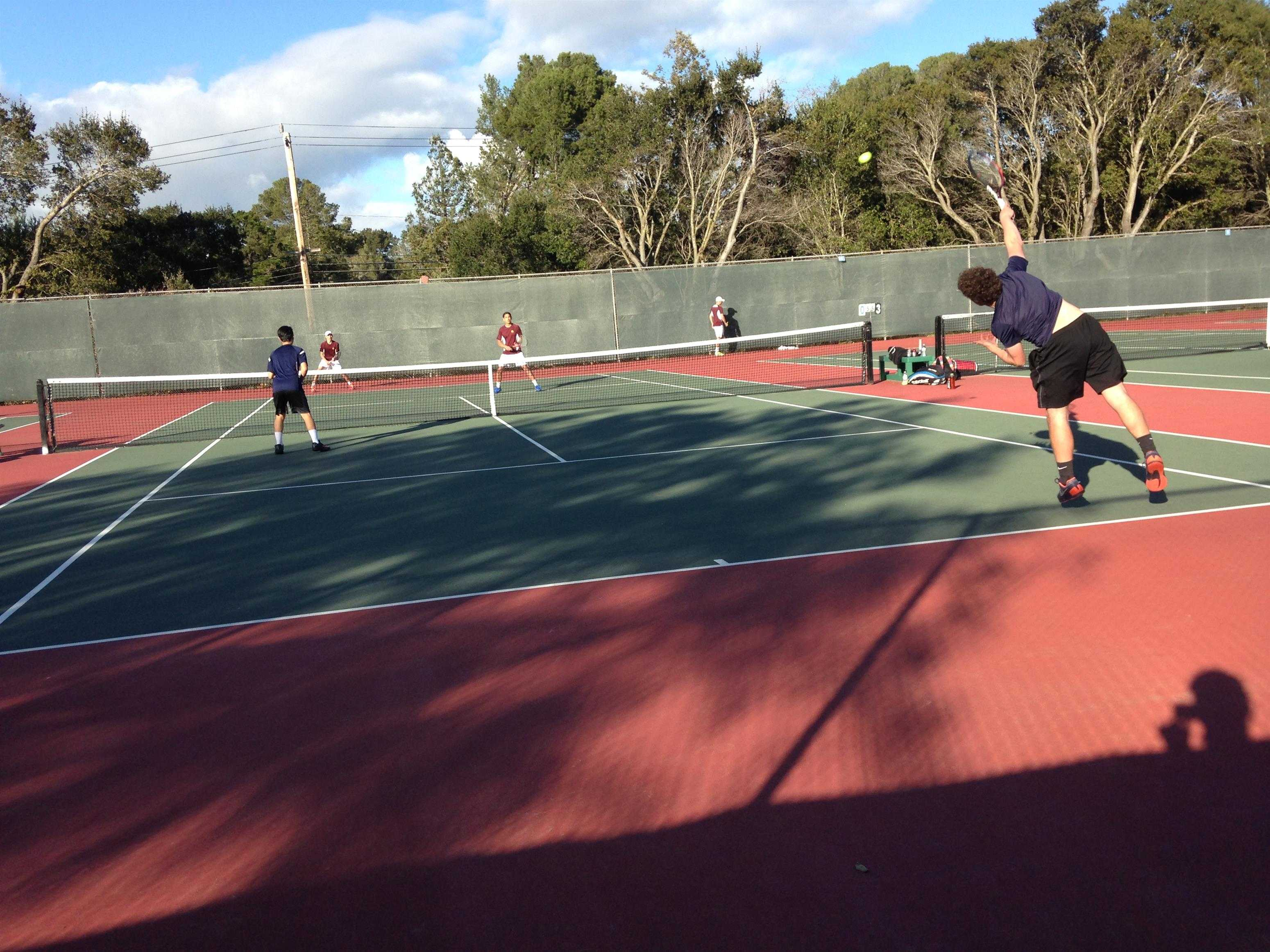 Freshman Ben Barde serves the ball in his doubles match as he and his teammate fight for the victory.