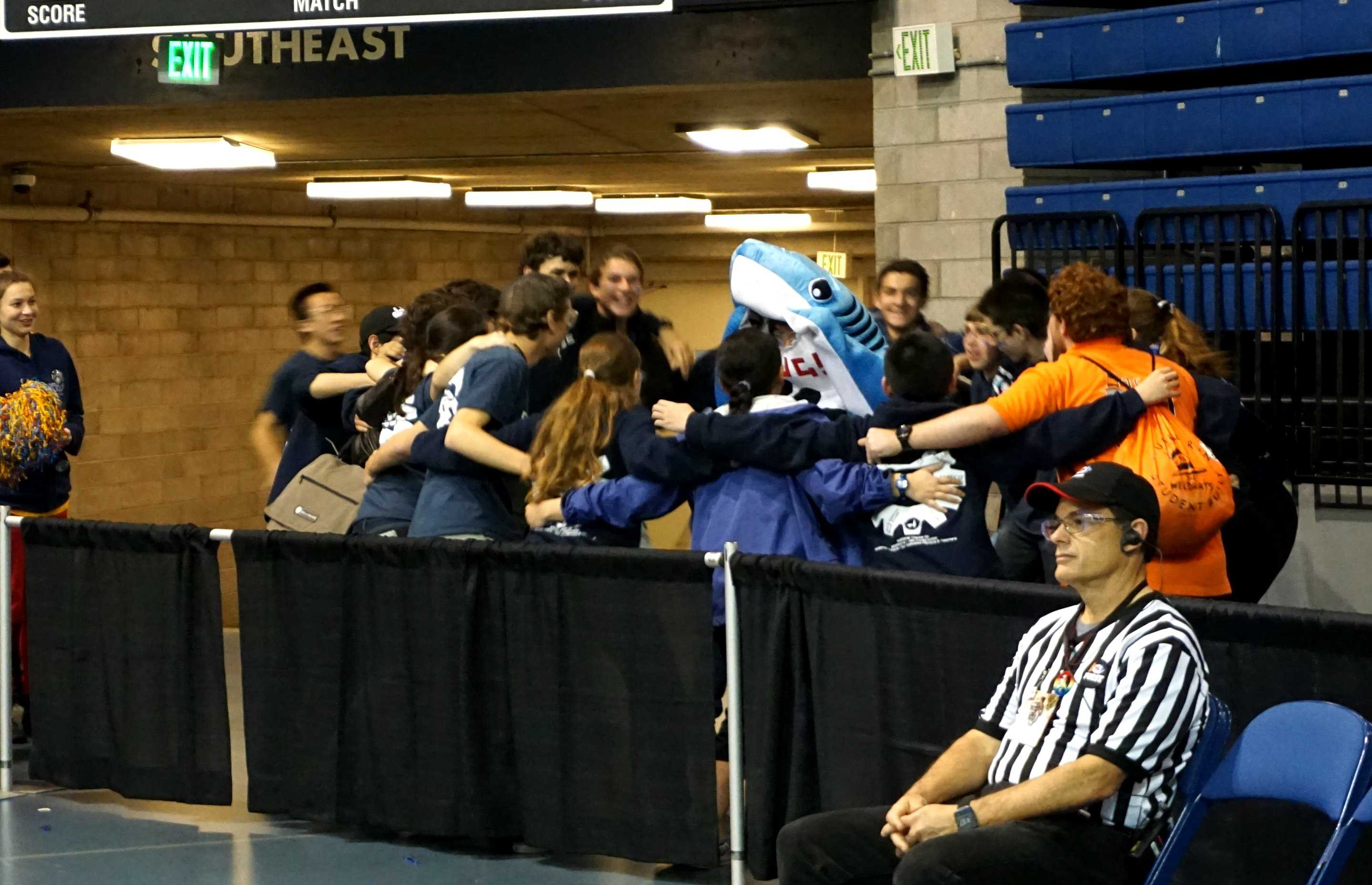 Deep Blue celebrates the results of their win at Sacramento Regionals with a group hug, including the team's mascot.