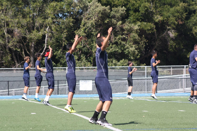 Both+varsity+and+JV+football+teams+warm+up+with+Carlmont+jumping+jacks.+