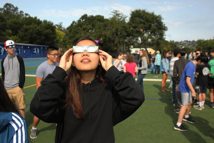 Mandy+Zhang%2C+a+senior%2C+uses+her+glasses+provided+by+Carlmont+parent+funding+to+view+the+solar+eclipse.