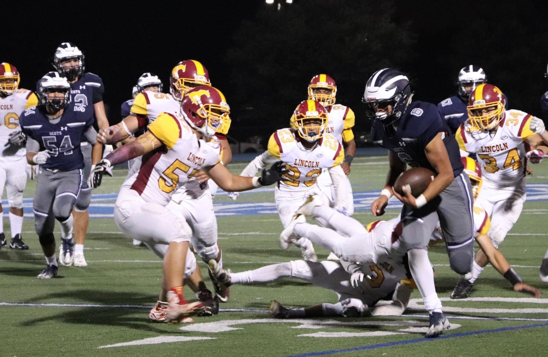 Eleventh-grader Julian Morin scores a touchdown on the left sideline.