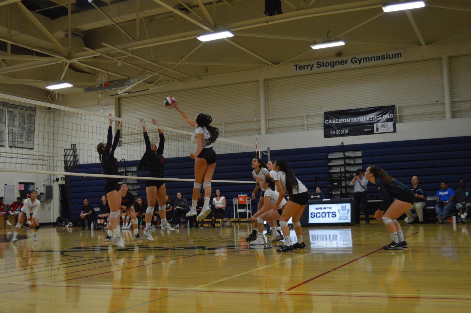 Maya+McClellan%2C+a+senior%2C+tips+over+the+net+to+score+in+the+fourth+set.