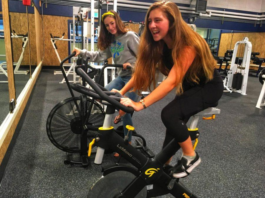 Freshmen+Nyah+Dompier-Norrbom+and+Mia+Messina+test+out+the+new+spin+bikes.+%22The+new+weight+room+is+really+nice.+It+looks+like+a+college+weight+room%2C%22+said+Messina.