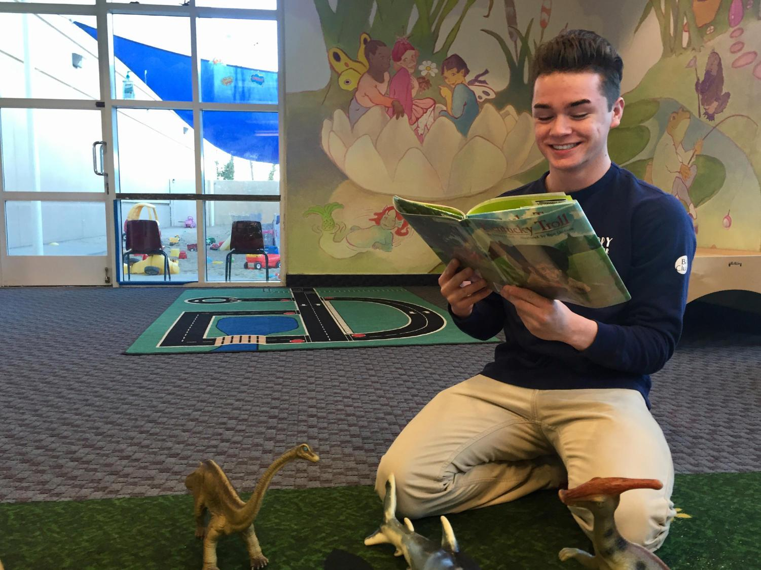 Ryan Huskey, a junior, reads to toddlers as a part of his job as a Childcare Associate at the Bay Club in Redwood Shores.