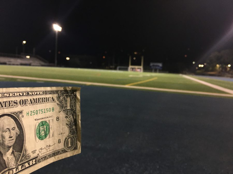 A+dollar+bill+displayed+in+front+of+the+Carlmont+football+field.