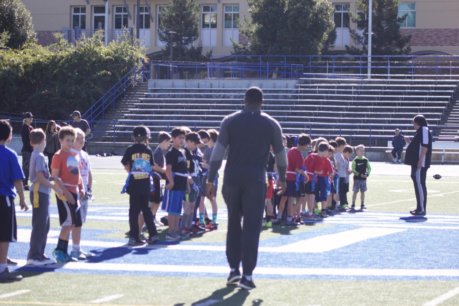 Players gather at Carlmont High School's field for a flag fooball clinic, with special guest NFL tight end Kevin Greene.