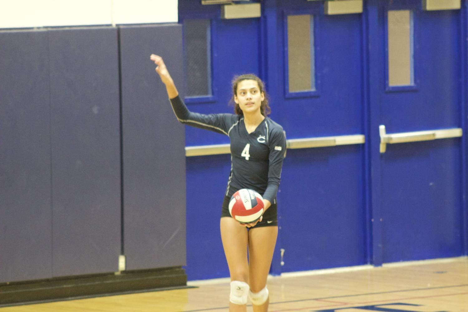 Sophie Srivastava, a senior, gets ready to serve the ball.