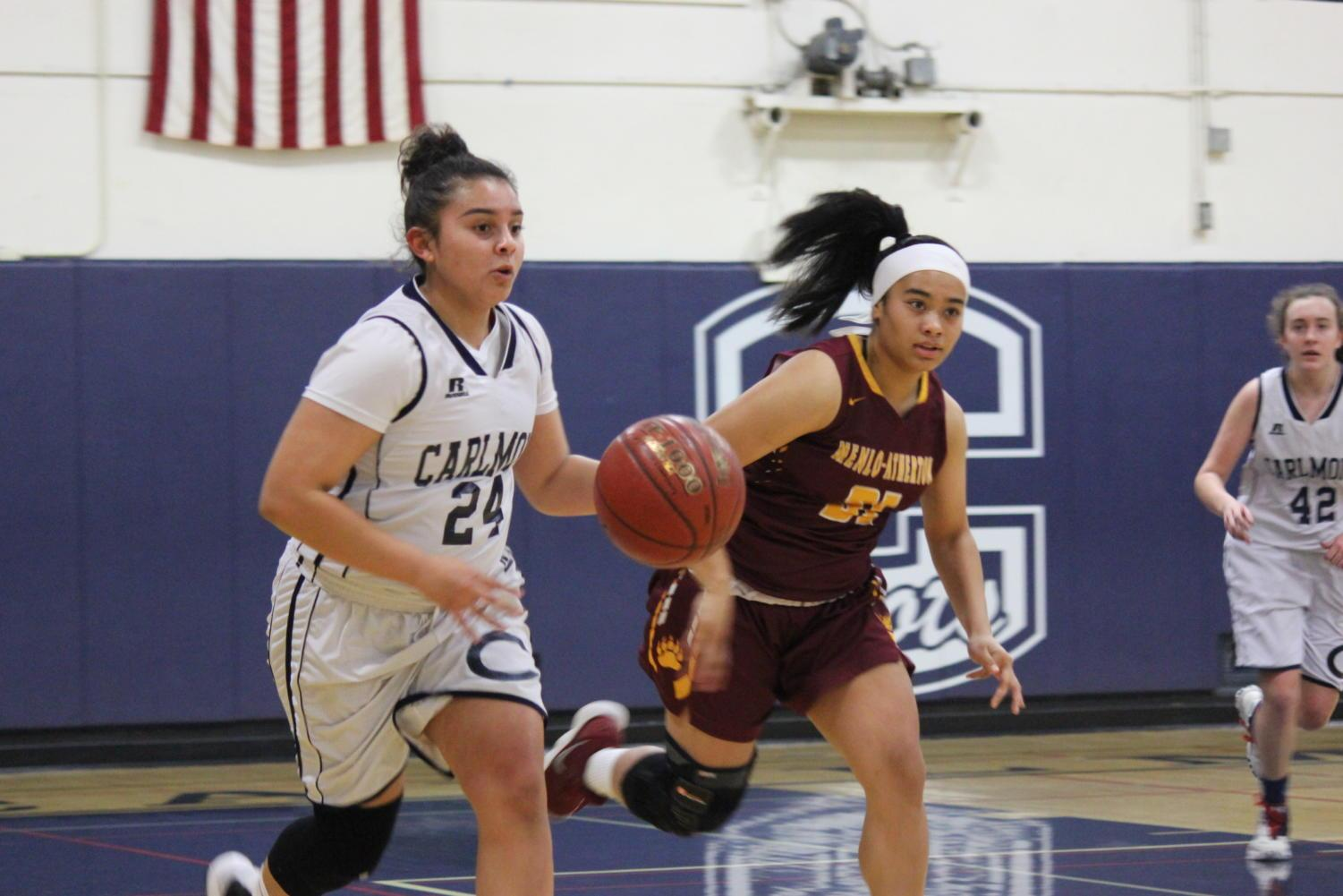 Junior Izzy Rodriguez tries to outrun a Menlo Atherton player while looking for an open player to pass to.