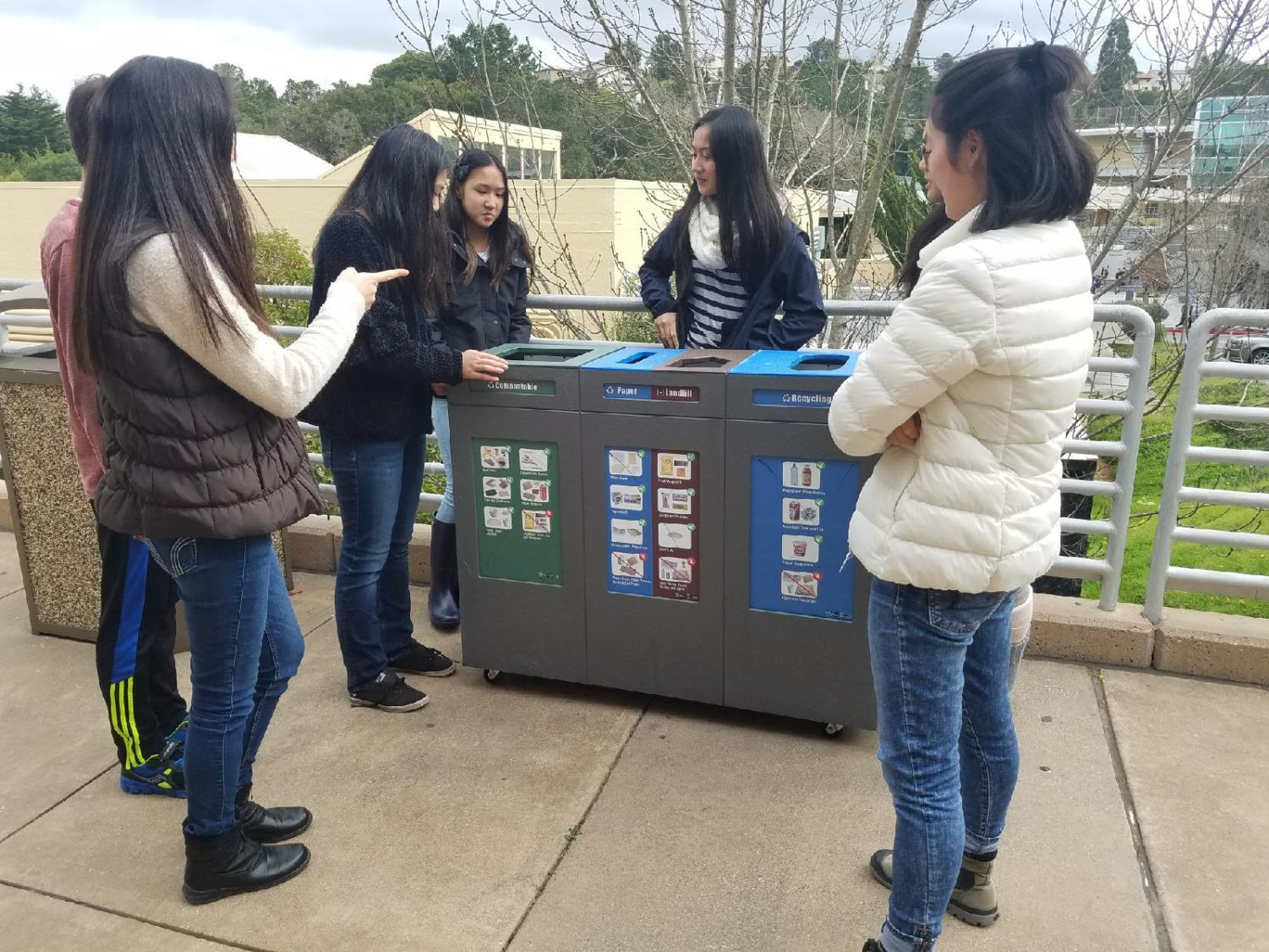 The Green Team stands outside during one of their meetings and discusses the tri-bin system.