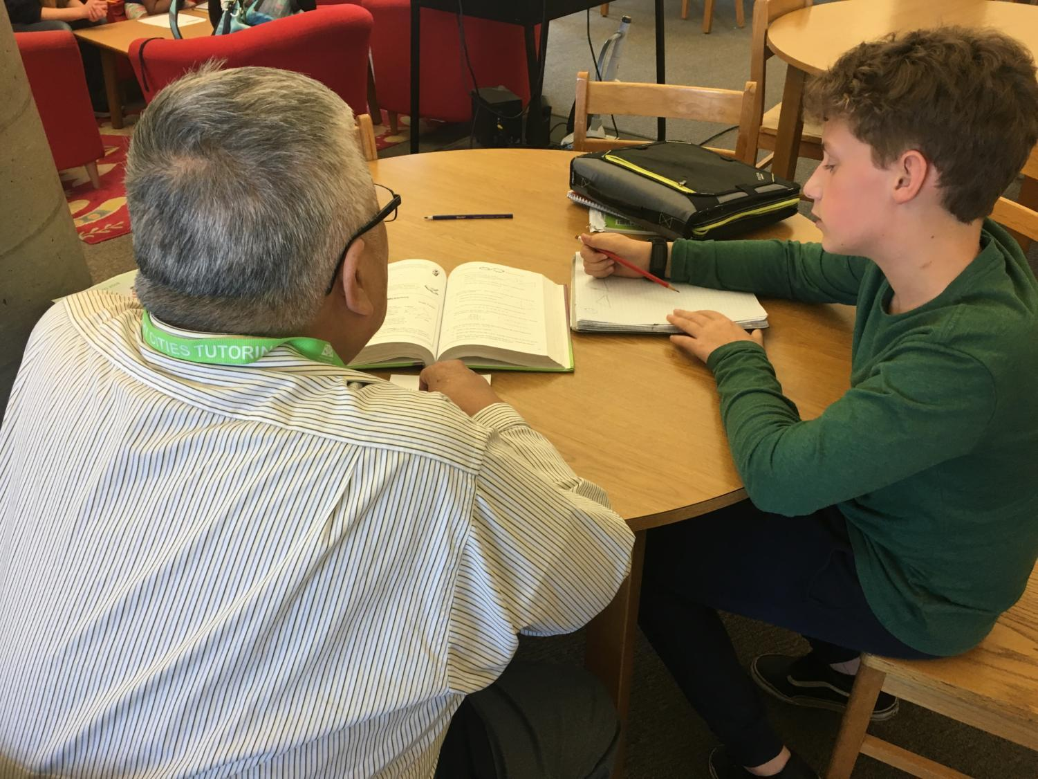 Healthy Cities tutor Kelvin Lee helps eighth grader Charlie Baker with his homework at the Tierra Linda Middle School Library
