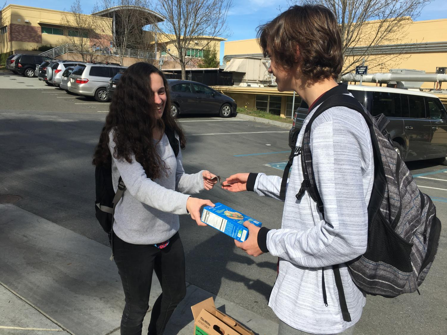 Luke Hendrickson, a sophomore, buys a box of Trefoils from Ana Alvarez-Rutz, a Girl Scout.