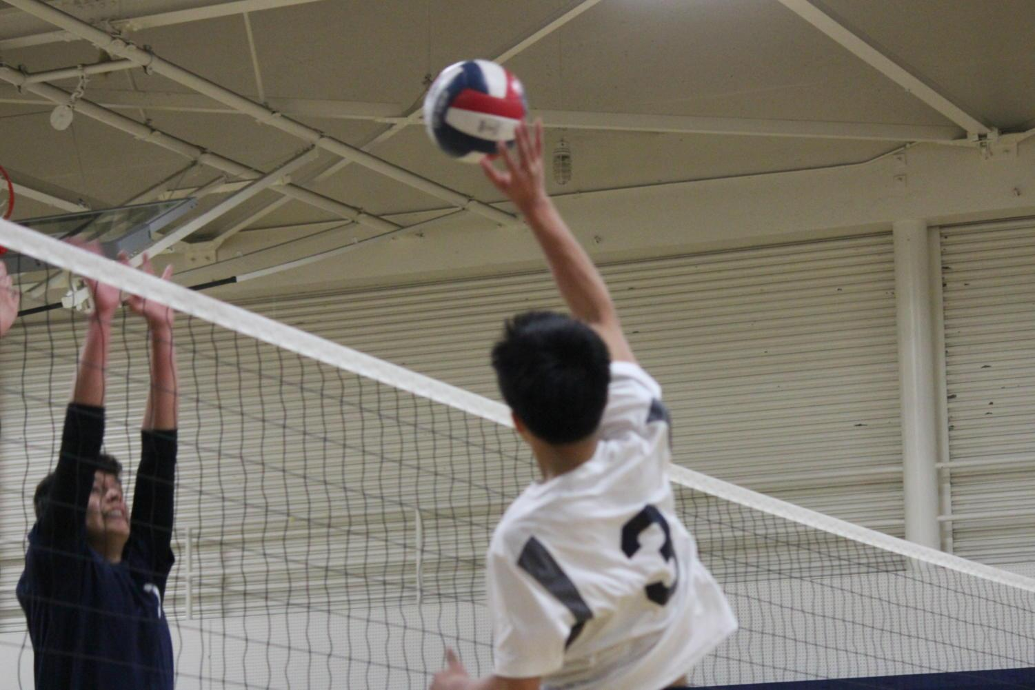 Freshman Justin Wong hits the ball over the net, getting past the Eagles blocker.