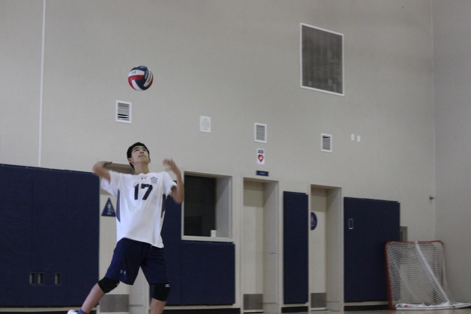 Freshman Ryan Tomita rises up for a serve.