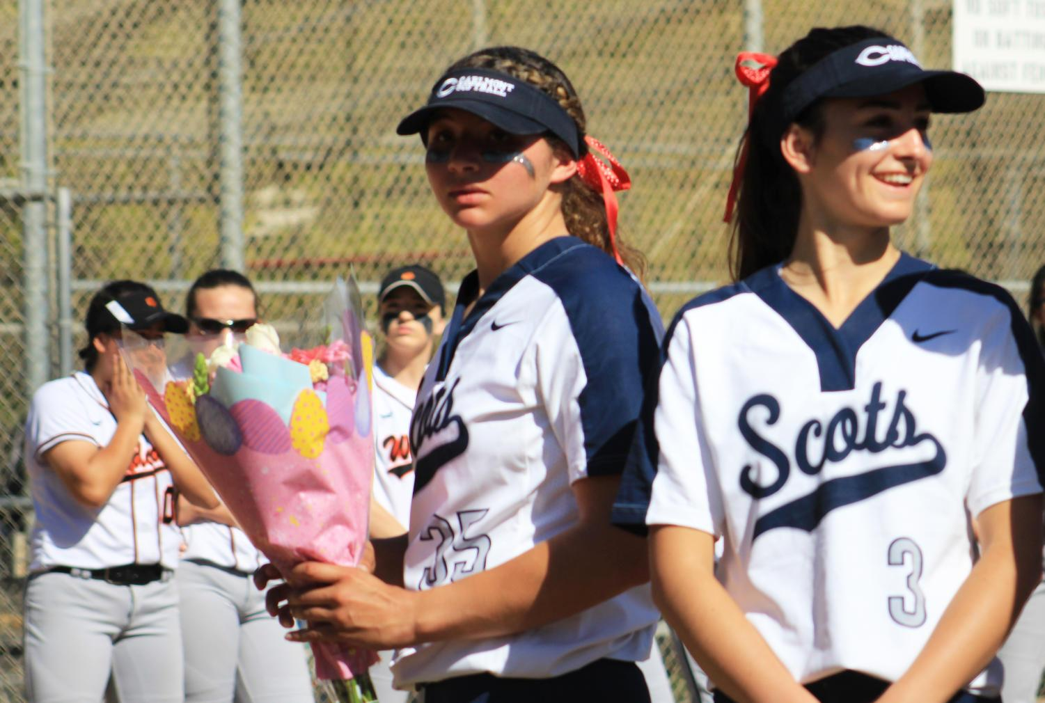 Senior captain and pitcher for the varsity team, Mailey McLemore, holds a bouquet of flowers for Jim Liggett's wife, Charlene Liggett.