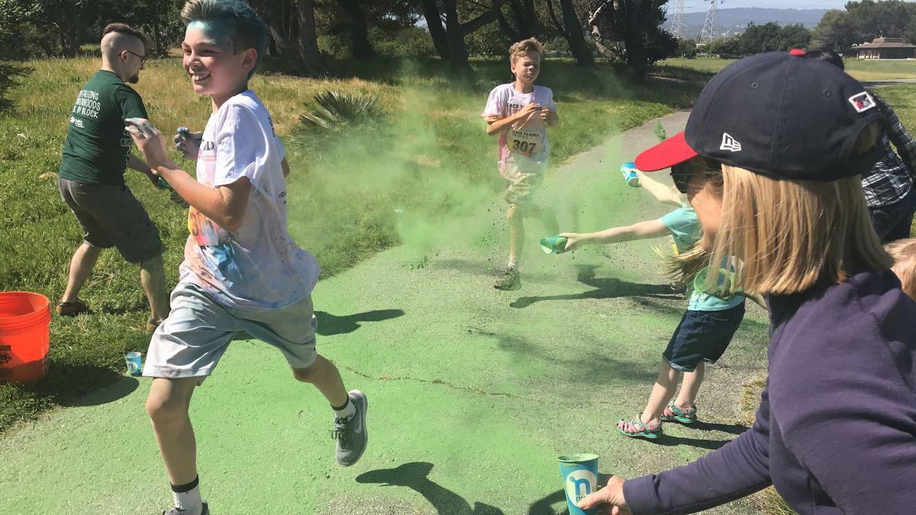 Runners get color thrown at them by volunteers. Some of the volunteers, like Patrick, Hayden, and Zach Tucker, came to the run as a family event to have fun.