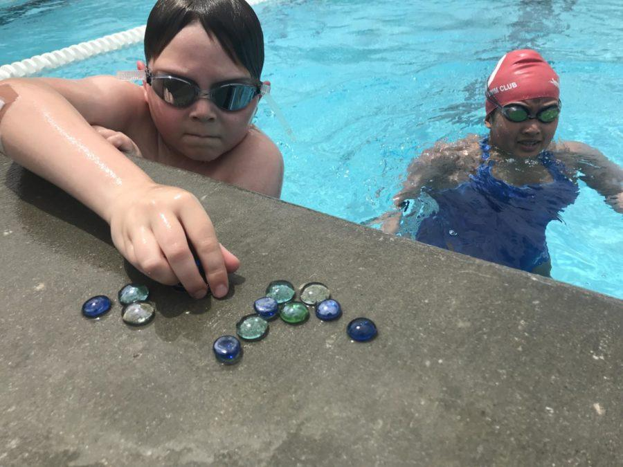Participants+of+the+Swim-a-Thon+collect+clear+marbles+to+swim+with+across+the+pool.