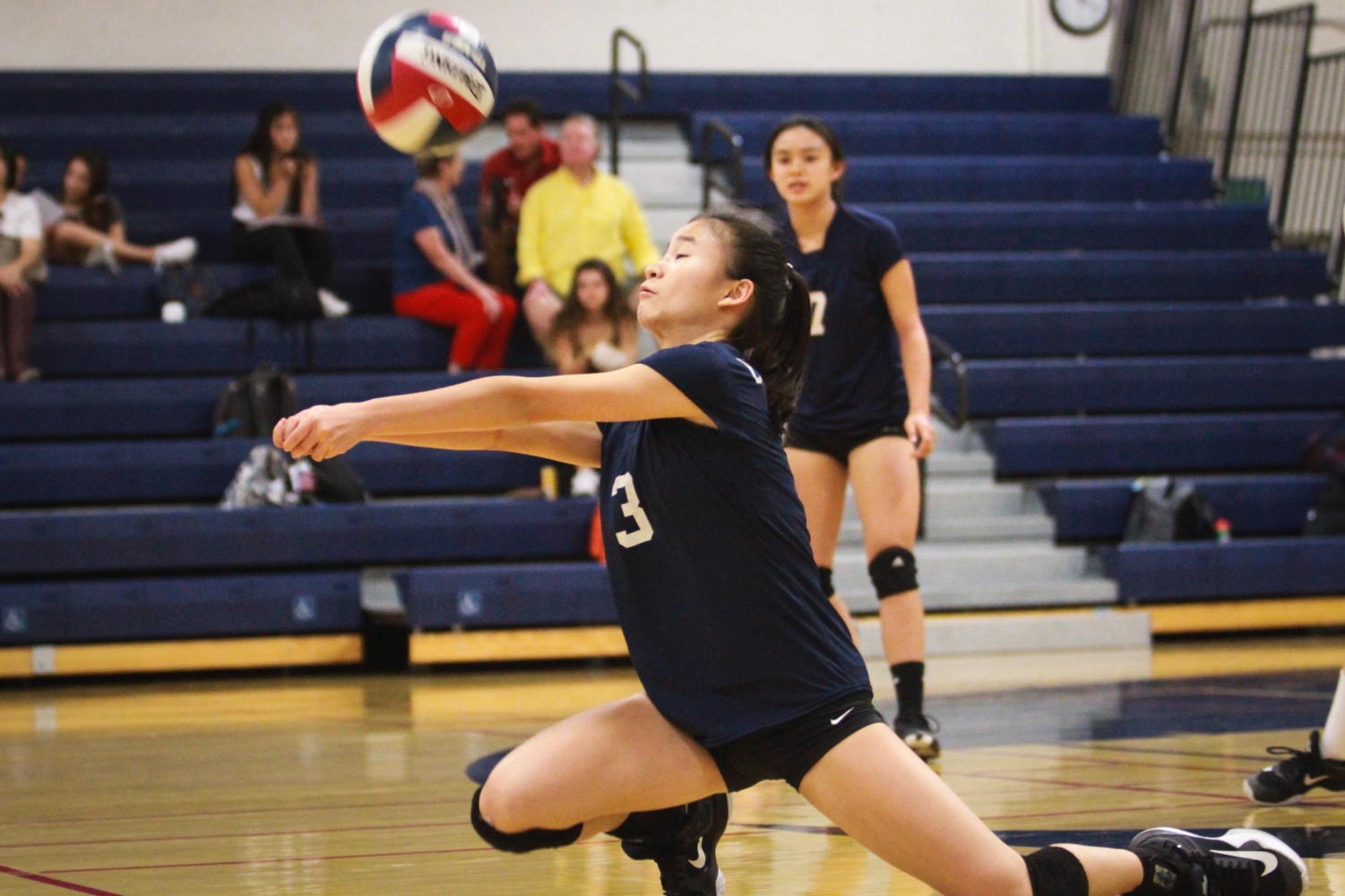 Claire Tseng, a freshman, digs up the ball for her team.