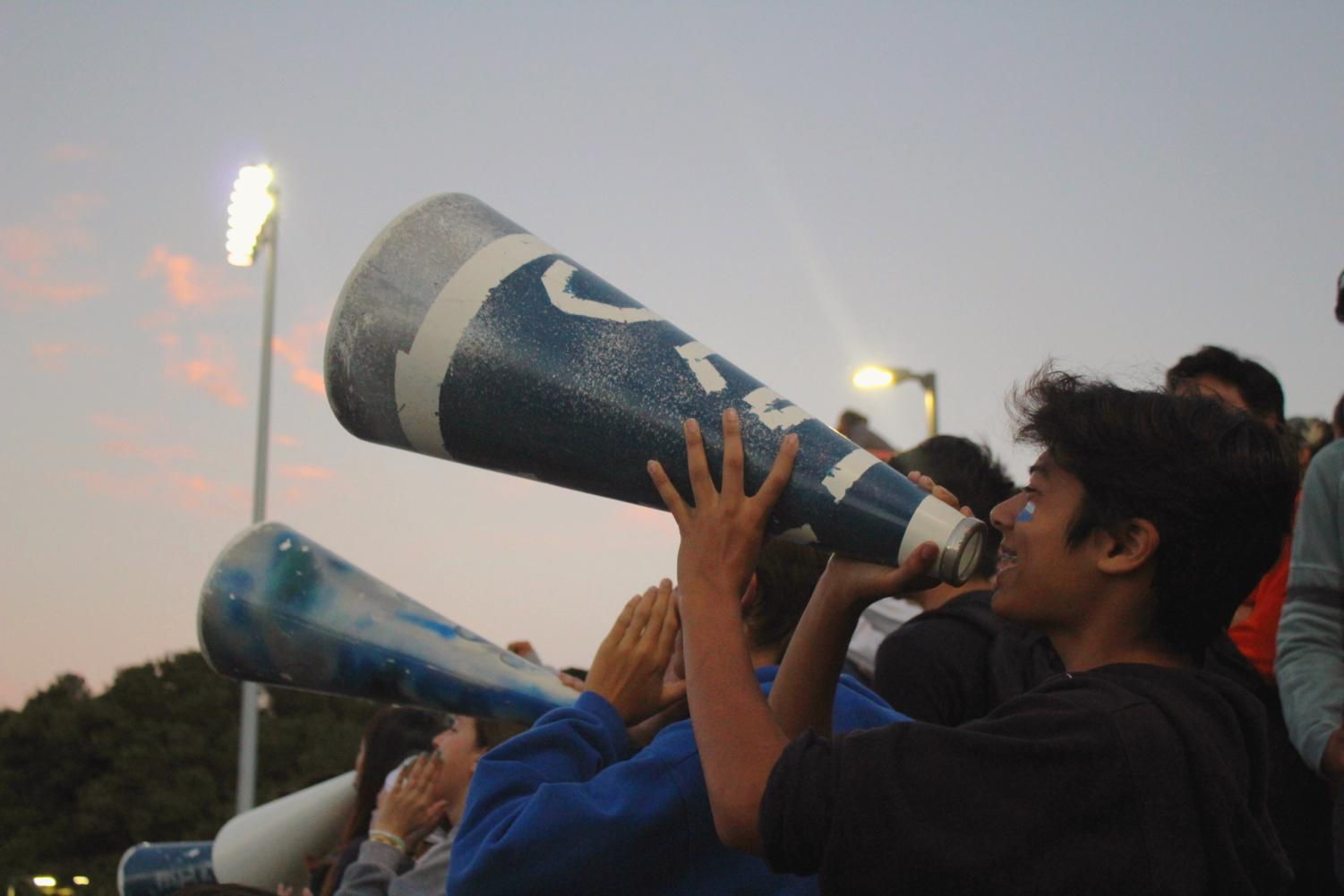 The Screamin' Scots use megaphones to cheer for the football team and raise spirit.