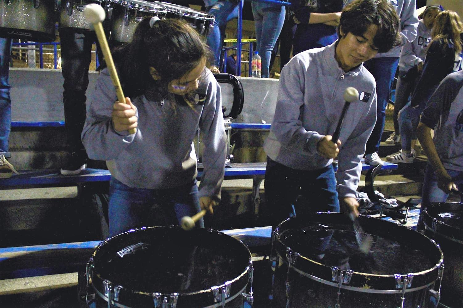 Juniors Isabel Coughlin and Niko Haller play the bass drums at a football game.
