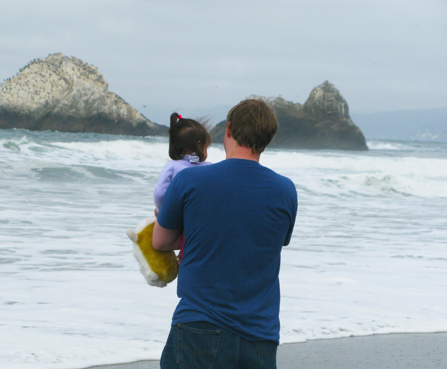 A+child+holds+onto+her+corgi+stuffed+animal+as+she+watches+the+waves+with+her+father.