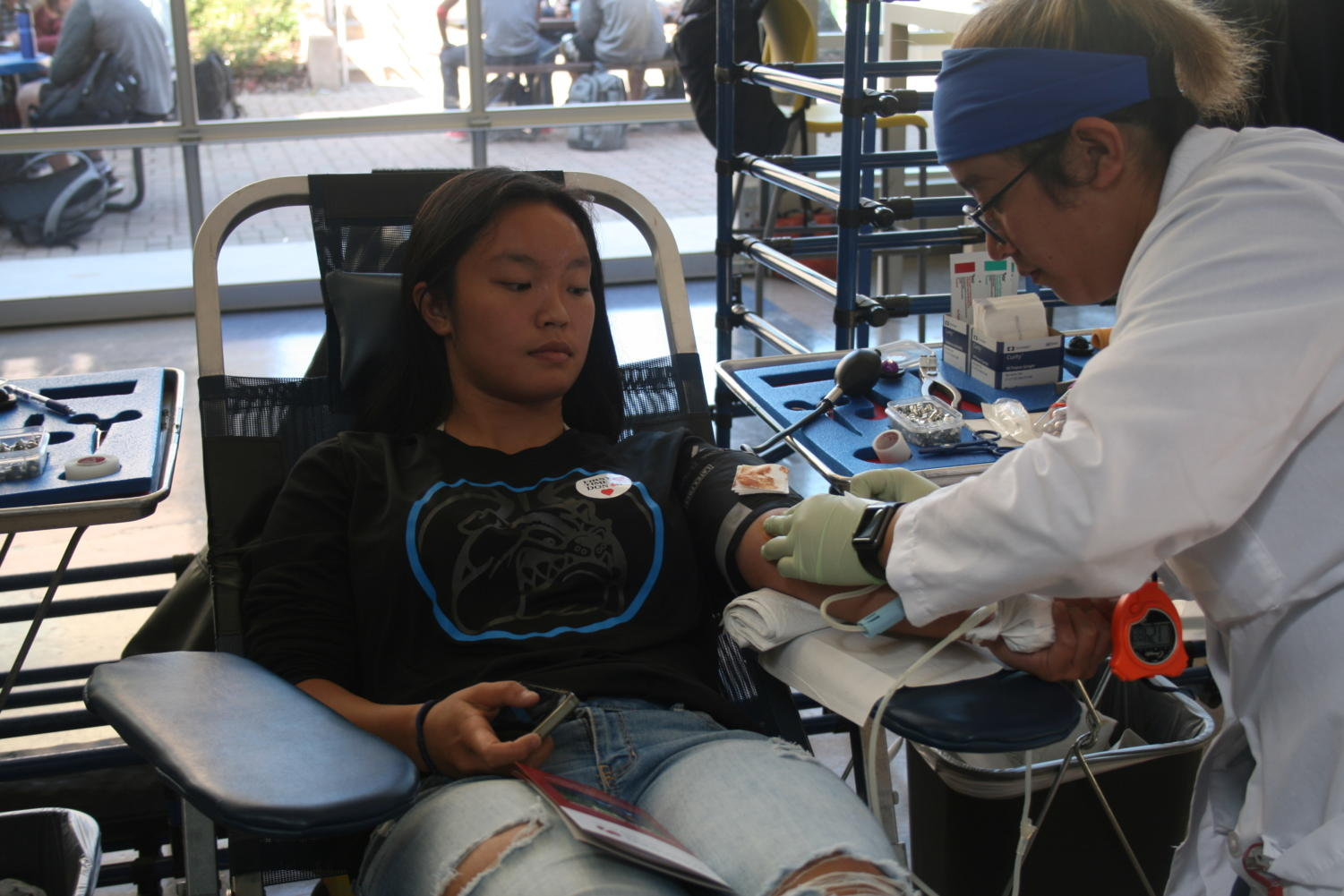 Madison Palarca-Wong, a senior, calmly watches a blood technician draw her blood.