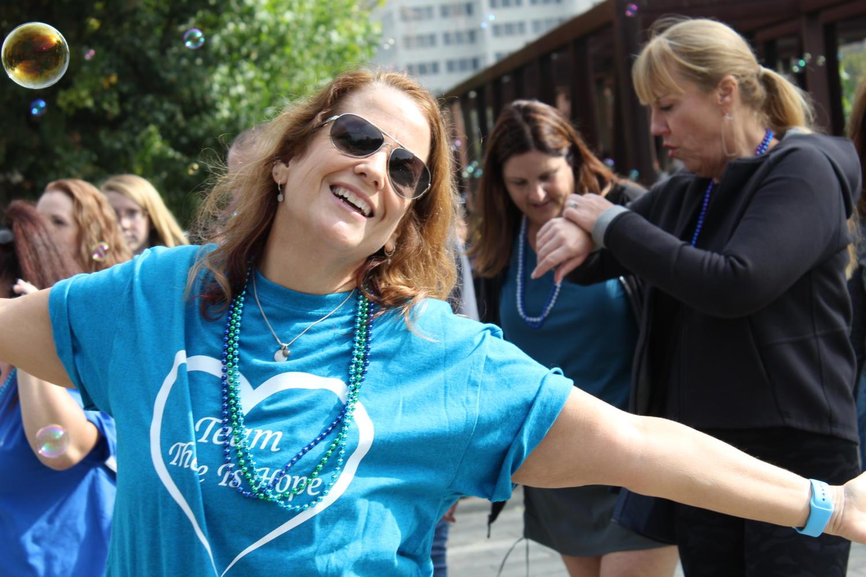 A sponsoring team member celebrates the end of her walk.