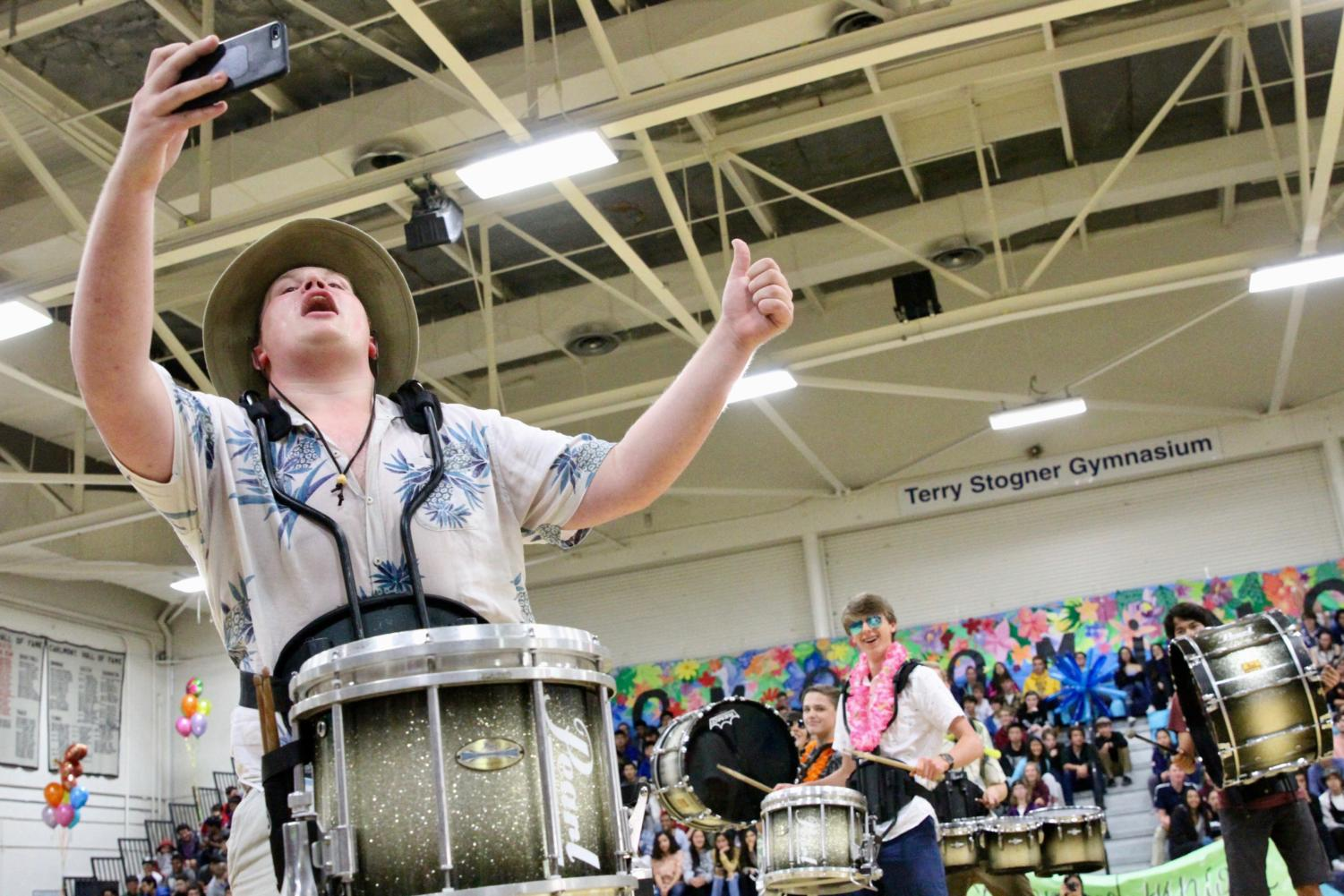 Drumline's captain, William Yonts, a senior, poses for a selfie with his ensemble during the Homecoming assembly on Oct. 25.