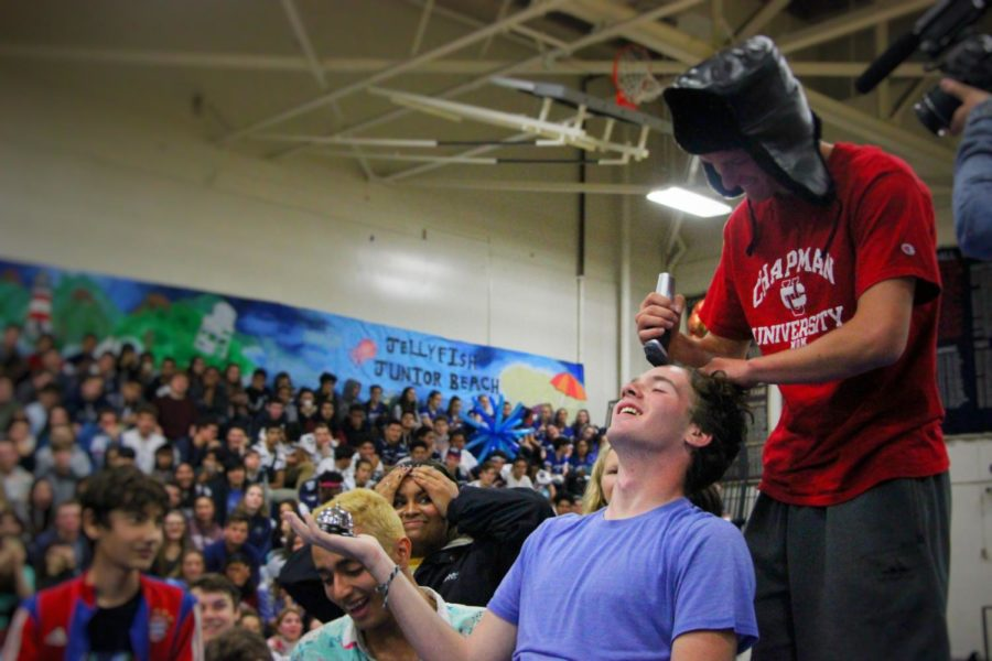 Tim+Krassiev%2C+a+senior%2C+shaves+the+head+of+George+Sharkey%2C+a+senior%2C+during+an+activity+in+the+homecoming+assembly.