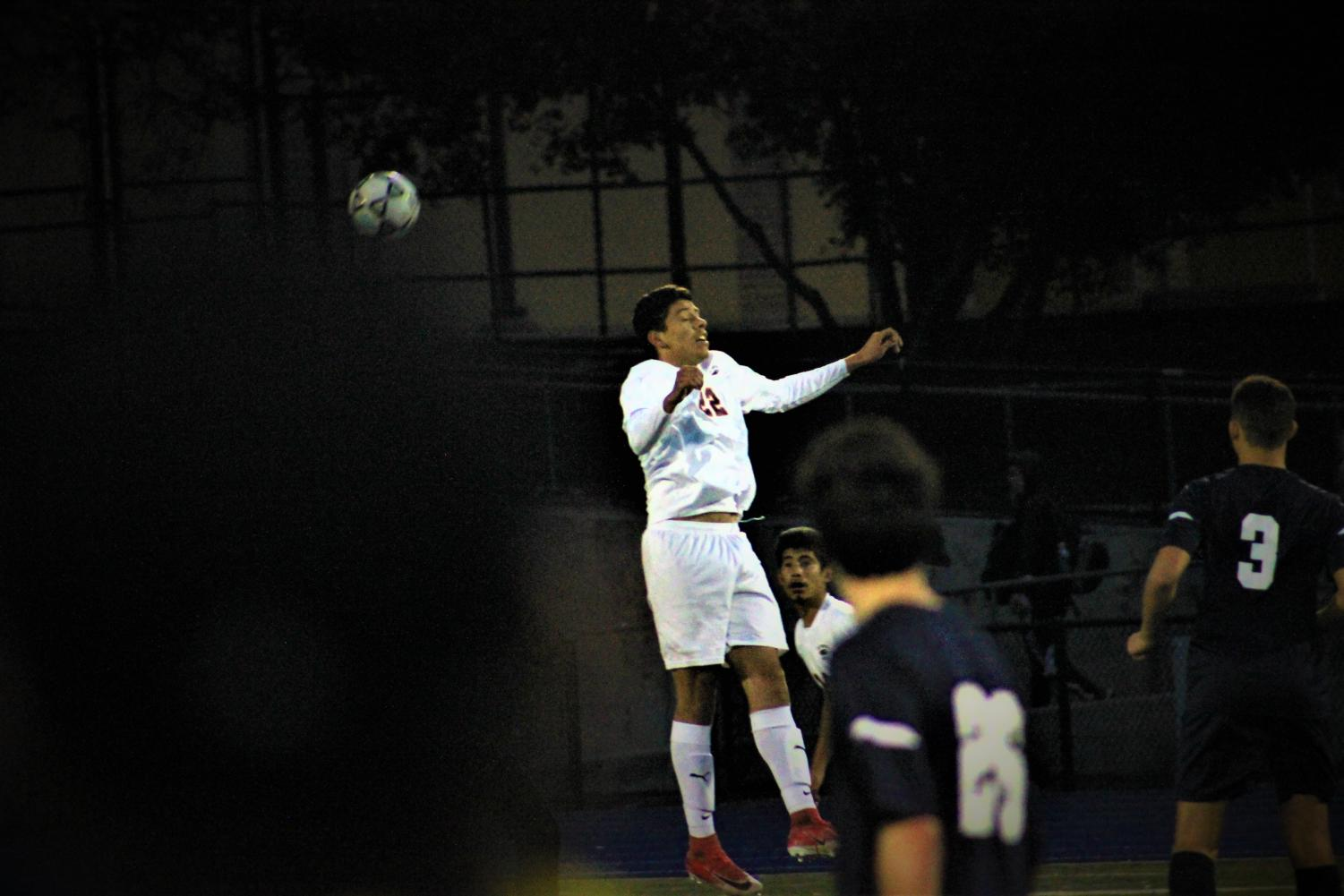 A member of the JV boys soccer team leaps for a header in the middle of a game.