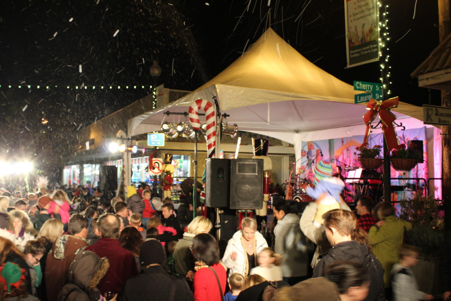 Crowds of people stand to watch the performance under fake snow generated by a bubble machine.