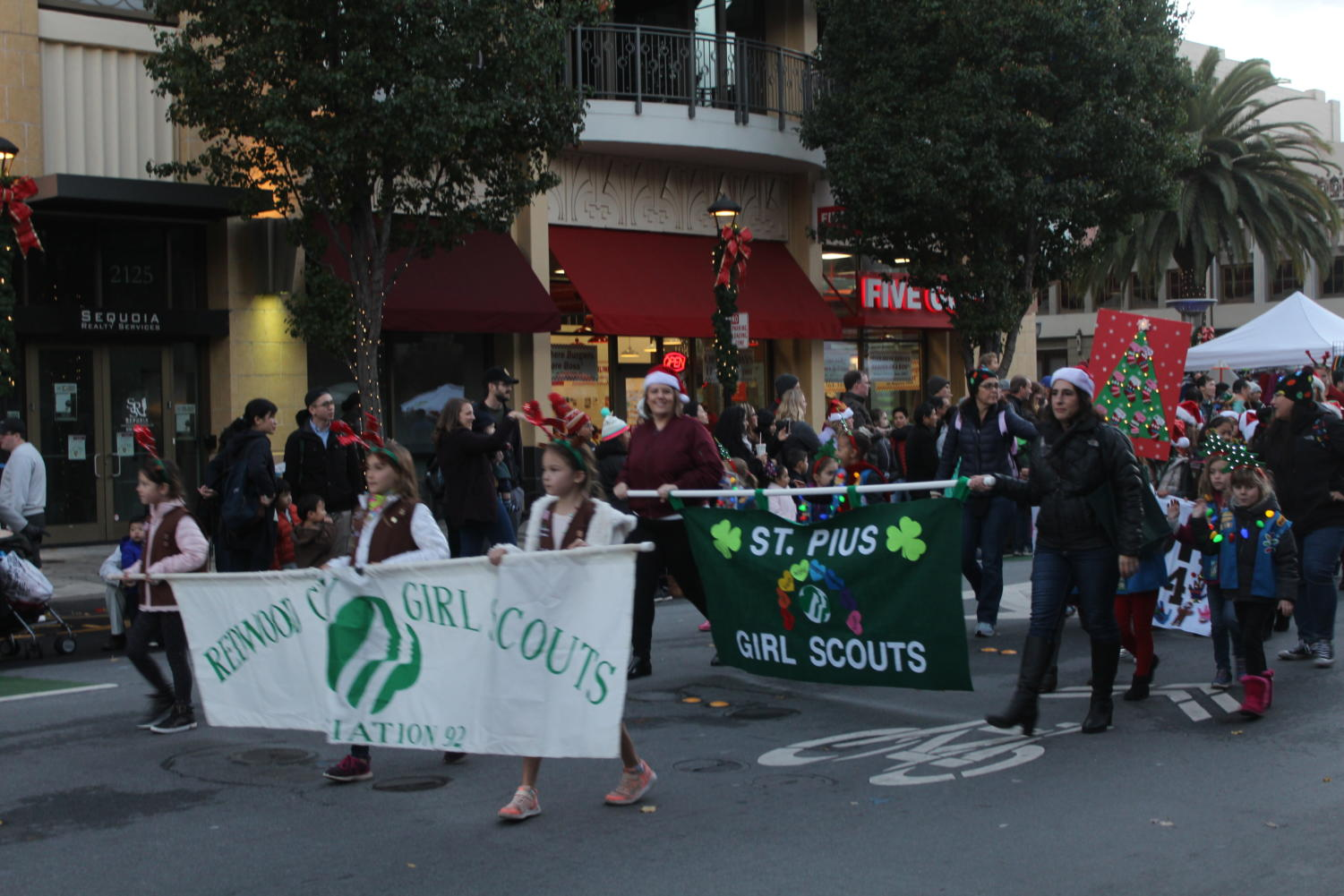 The+St.+Piu%27s+Girl+Scouts+walk+through+the+parade+carrying+banners.+Individual+troops+cycled+through+the+parade+later+on.