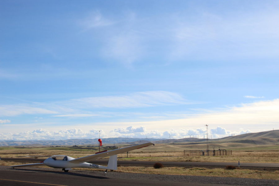 A+single-seat+club+sailplane+sits+off+to+the+side+of+a+taxiway+at+Byron+Airport.