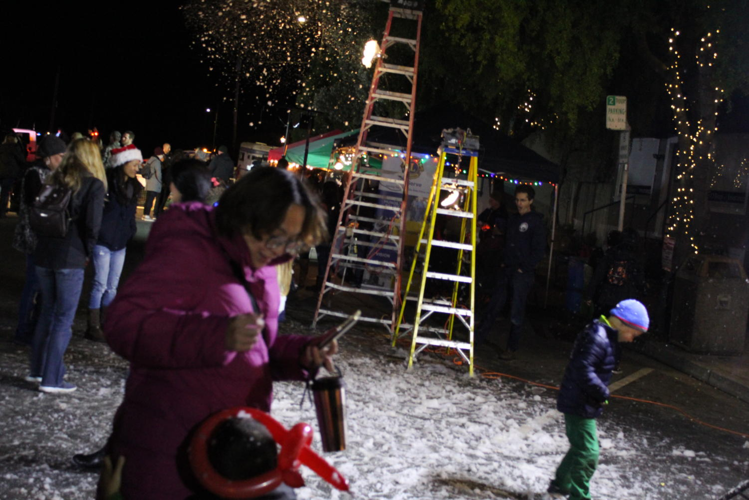People play in the fake snow pumped out by snow machines.