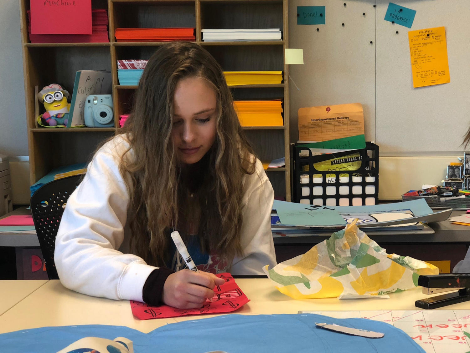 Sasha Belov, a freshman, works on a poster for the Snowman Project.